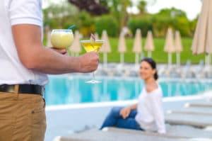 Mann bringt Frau am Pool Cocktails
